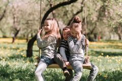 Three little friends sitting on a swing in the garden on a spring day. The concept of a happy childhood royalty free stock photo