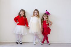 Three little girl girlfriends in red and white dresses