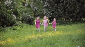 Three little girl holding by hands running on green grass at garden surrounded by air bubble blower stock video footage