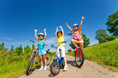 Three little girls on a bikes outsides. Three little girls with bicycles raise hands up on a paved road on sunny day in the park Royalty Free Stock Photos