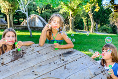 Three little girls blowing bubbles in the park. Three little girls are blowing bubbles in the park stock photography