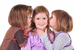 Three little girls are chatting, isolated over. White royalty free stock images