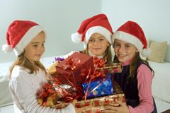 Three little girls with christmas presents. And santa hats royalty free stock photos