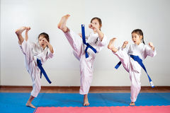 Three little girls demonstrate martial arts working together. Fighting position, active lifestyle, practicing fighting techniques stock photo