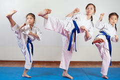 Three little girls demonstrate martial arts working together. Fighting position, active lifestyle, practicing fighting techniques stock image