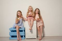 Three little girls eat sweet cake with cream cupcake stock photos
