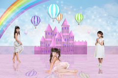Three little girls in front of a pink fairy castle Stock Images