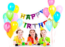 Three little girls having fun at the birthday party. Royalty Free Stock Photography