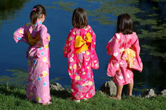 Three Little Girls in Kimonos. Three little girls standing next to pond in kimonos royalty free stock photo