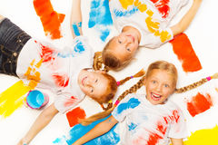 Three little girls laying on the painted floor Stock Images