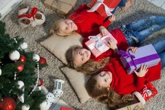 Three little girls lie near a Christmas tree with gifts new year holiday. Three little girls lie near a Christmas tree with gifts new year royalty free stock image