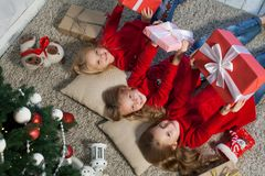 Three little girls lie near a Christmas tree with gifts new year holiday. Three little girls lie near a Christmas tree with gifts new year stock image