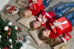 Three little girls lie near a Christmas tree with gifts new year holiday. Three little girls lie near a Christmas tree with gifts new year royalty free stock images