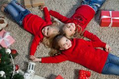 Three little girls lie near a Christmas tree with gifts new year holiday. Three little girls lie near a Christmas tree with gifts new year stock photo