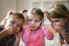 Three little girls with mobile phone. stock photo