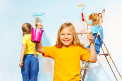 Three little girls painting the wall. Pretty smiling girl in yellow performs painting accessories, other two painting the wall in blue Stock Photography