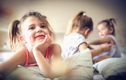 Three little girls playing in bed. stock photography