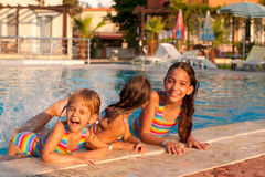 Three little girls playing in the pool. Three little girls (sisters) playing and splashing in the pool Stock Image
