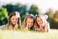 Three little girls showing OK with their hands. Stock Photo