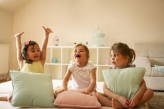 Three little girls sitting on bed. Little girls at home together stock photography