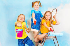 Three little girls smile on a background of wall Stock Image