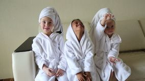 Girls in white coats with towels on their heads. Three little girls after swimming in the pool are sitting on the couch stock video