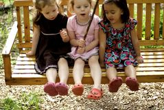 Three little girls on swing stock photography