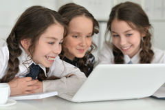 Three little girls using a laptop Stock Image