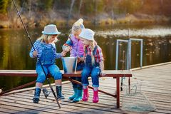 Three little happy girls brag about fish caught on a fishing pole. Fishing from a wooden pontoon royalty free stock images