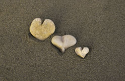 Three Little Heart Rocks. Three rocks in the shapes of hearts lay embedded into the sand Royalty Free Stock Images
