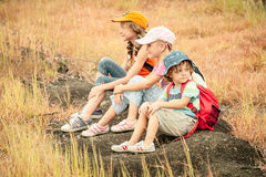 Three little kids with backpack sitting on the footpath in the m Stock Images