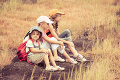 Three little kids with backpack sitting on the footpath in the m Royalty Free Stock Photography