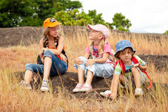 Three little kids with backpack sitting on the footpath in the m Stock Photography