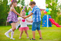 Three little kids dancing roundelay. Three little kids celebrating birthday dancing roundelay Stock Photography