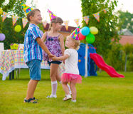 Three little kids dancing roundelay. Three little kids celebrating birthday dancing roundelay Royalty Free Stock Photo