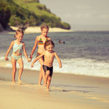 Three little kids running on the beach Royalty Free Stock Images