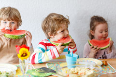 Three little kidseating healthy food watermelon Stock Image