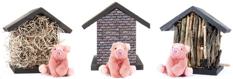 Three Little Pigs. Three houses made of straw, brick and sticks each with a pink pig in front Stock Photos