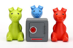 Three little pigs guarding a safe. Green, Blue and Red pigs around  toy safe Stock Photo