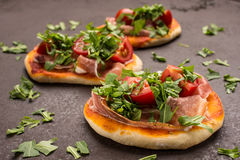 Three little pizza with tomato, rucola and parma ham Stock Photography