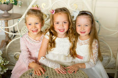 Three little princess sit around the table Royalty Free Stock Photography