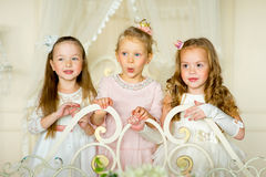 Three little princess standing on the bed. In classic dress and vintage atmosphere of the room stock photography