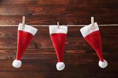Three little Santa Claus hat hanging on a string against wooden rustic background. Christmas and New year concept. Greeting card. Stock Photos