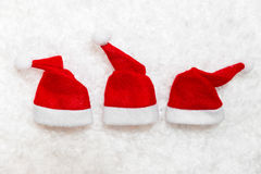 Three little santa claus pointed caps in the snow Royalty Free Stock Images