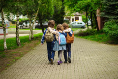 Three little school students, two boys and the girl, go in an embrace to school Stock Images