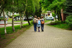 Three little school students, two boys and the girl, go in an embrace to school Stock Image