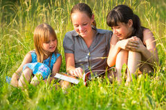 Three little sister reading book in natural Royalty Free Stock Image