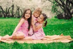 Three little sisters having a lot of fun playing together outdoor in summer park. On vacation Stock Photos