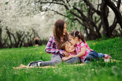 Three little sisters having a lot of fun playing together outdoor in summer park on vacation Stock Photos