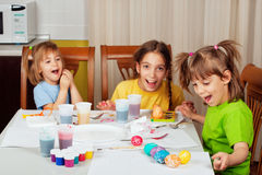Three little sisters painting Easter eggs Stock Photo
